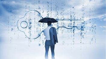 Businessman with an umbrella looking at a giant key with blue sky on the background
